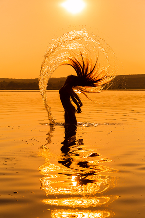 resort beach: Silhouette of young girl in the water splashing their hair against sunset