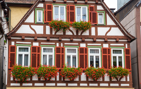german: Wall of old house with potted flowers on windows, historic old German town Calw, autumn city landscape with flowers