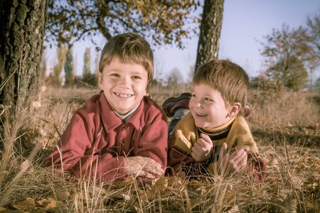 young boys: Two smiling boys lying down on withered grass in autumn park, sepia toned image
