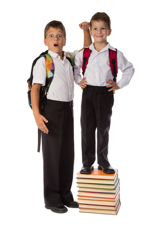 schoolboys: Two happy schoolboys standing with pile of books, isolated on white