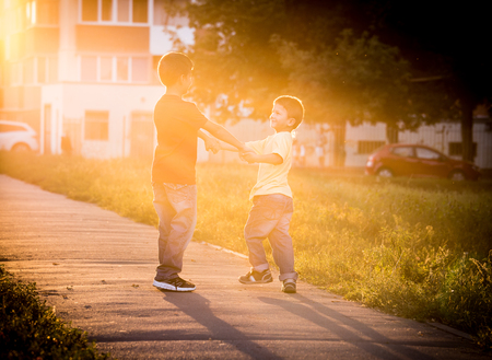 sideway: Two boys playing together on street with sun back light, toned image