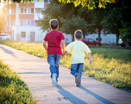 iluminado a contraluz: Dos niños que se ejecutan junto en la calle con el sol de nuevo la luz Foto de archivo