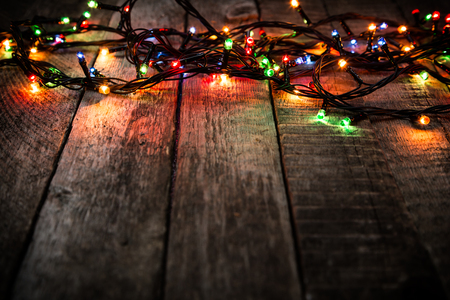 harsh light: Christmas lights on dark wooden rough background, empty space for text