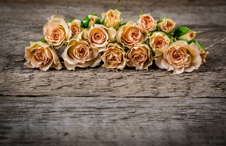 Bouquet of beige roses on wooden rogue table background with empty space for text