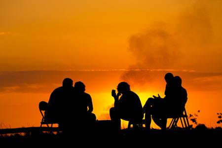 석양에 대하여 모닥불 근처에 앉아 캠핑에 다섯 사람의 실루엣