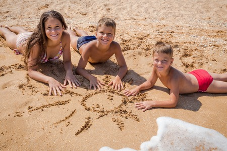 Three smiling kids lying on the beach playing together near water