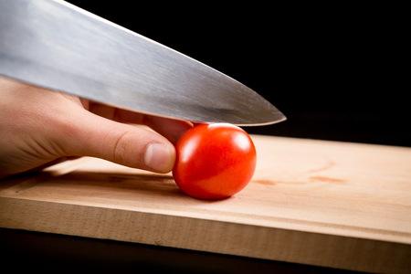 knife tomato: Cutting little red cherry tomato on wooden board