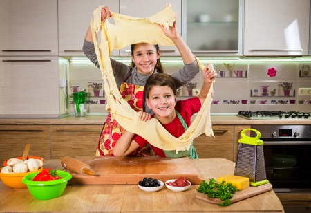Two funny kids kneading the dough, making the pizza