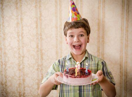 gateau anniversaire: Sourire garçon tenant un gâteau d'anniversaire, l'espace pour le texte Banque d'images