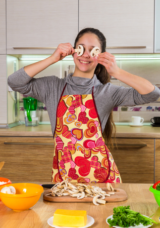Funny girl with mushrooms slices on eyes making the pizza photo