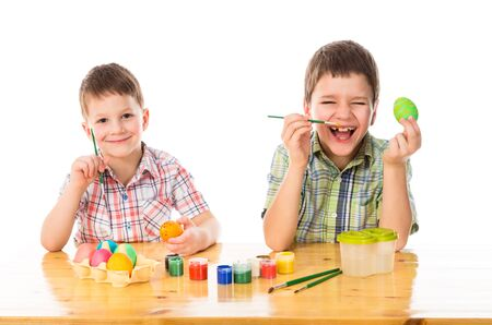 Two smiling boys painting easter eggs photo