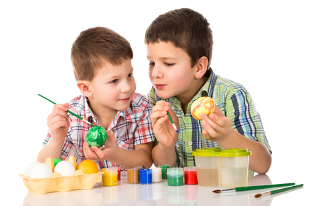 Two smiling kids painting easter eggs together at the table