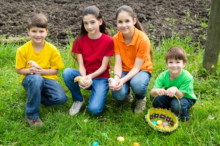 smiling kids at green grass holding a little chickens, easter co photo