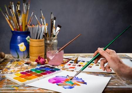 paleta de pintor: La mano sostiene el cepillo en la imagen en el estudio