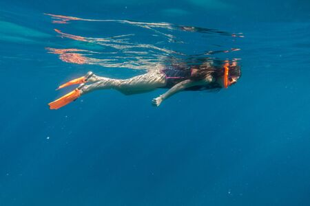 freediving: Girl in swimming mask and flippers dive in Red sea