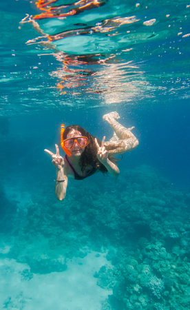 freediving: Girl in swimming mask dive underwater near coral reef Stock Photo