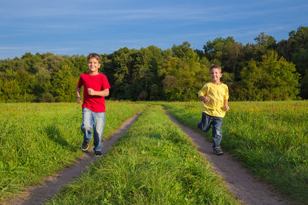 Two boys running together on rural road photo