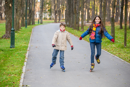 Two kids riding in autumn park on rollerblades photo