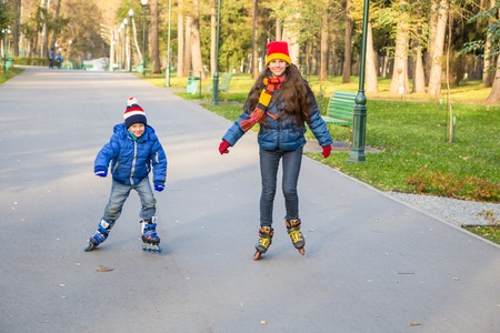 Two kids learning to ride in autumn park on rollerblades photo