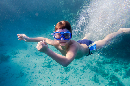 Boy in swimming mask deep dive in Red sea near coral reef