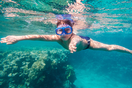 Boy in swimming mask dive in Red sea near coral reef