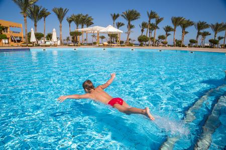 boy swim: Little boy jumping in the pool in hotel