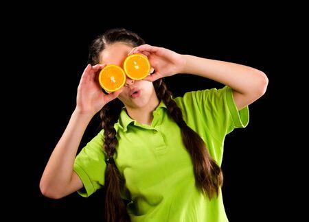 Surprised funny girl with sliced orange on eyes