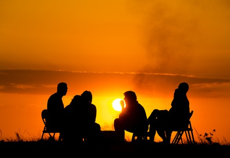 group of people in camping sitting near campfire against sunset Stockfoto