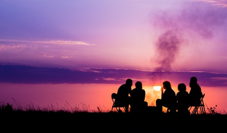 people sitting near campfire against sunset with copyspace Stock Photo
