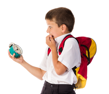 frightened schoolboy with alarm clock in hand Stock Photo