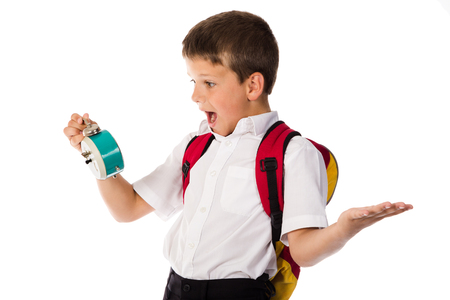 Amazed schoolboy with alarm clock in hand