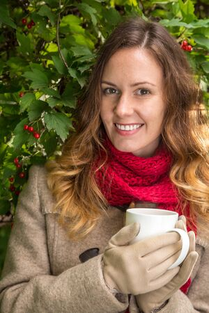 girl in warm clothes on autumn park holding a cup with hot tea