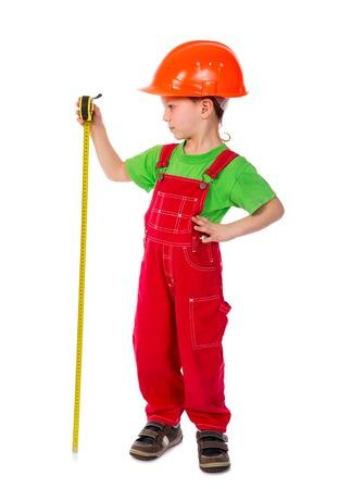 Little builder in helmet with ruler tape