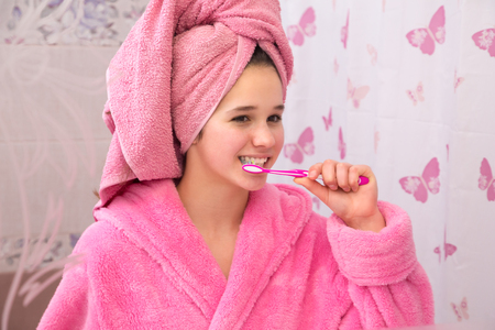 Young girl in bathrobe cleaning his teeth in the bathroom