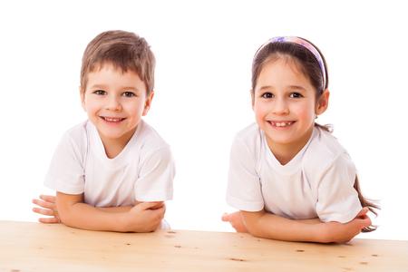 Due bambini sorridenti alla scrivania