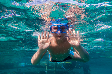 Boy in swimming mask dive in Red sea near pontoon