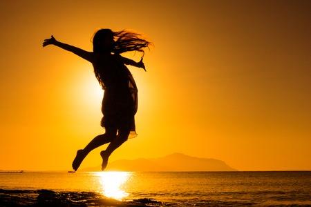 silhouette of girl jumping against sunrise