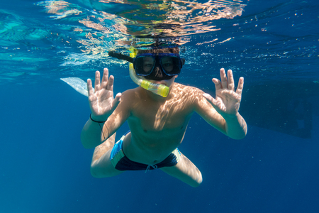 Boy in swimming mask dive in Red sea near yacht Stock Photo