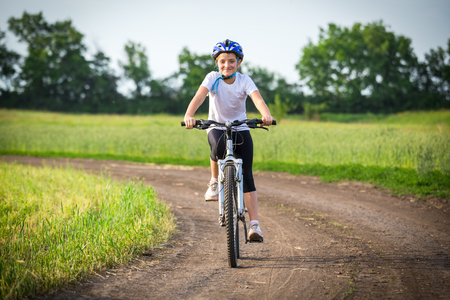 Smiling girl ride on bike on rural landscape Stockfoto