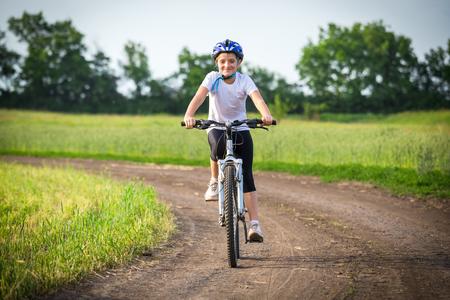 Fille souriante à vélo sur paysage rural