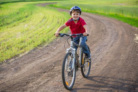 boy ride on bike at rural road