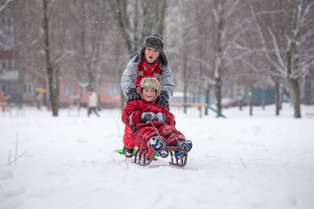 Two boys riding at the slide on snowy city