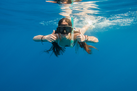 Girl in swimming mask dive in Red sea