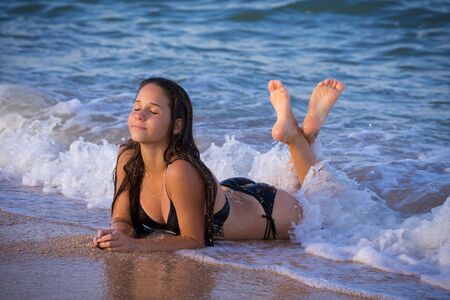 girl lying down on the surf at the sea