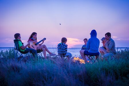 people sitting on the beach with campfire at sunset Stockfoto