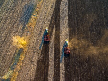 Aerial view to field with plowing agriculture machines and dust on ground, autumn landscape