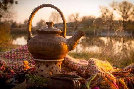 Hot teapot at autumn sunset on riverbank Imagens