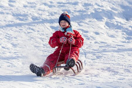 happy boy sitting at the sledge on snowy hill