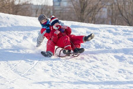 Two boys riding together at the sledge on snowy hill