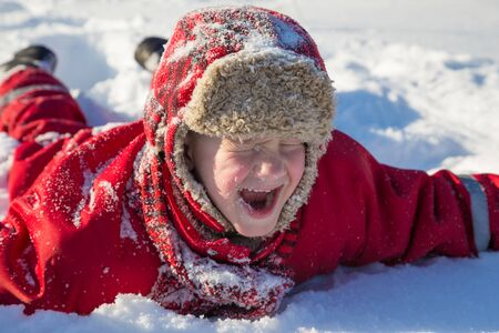 Adorable laughing boy at the snow background Imagens